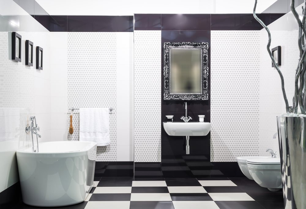 A gorgeous ornate mirror hangs above the wall-mounted sink that's fitted with a gooseneck faucet. This room is decorated with black framed wall arts and a large chrome vase over checkered flooring.