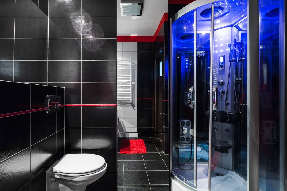 A modern toilet faces the hydromassage shower cabin in this master bathroom with a white towel rack and a red rug that stands out against the black tiled flooring.