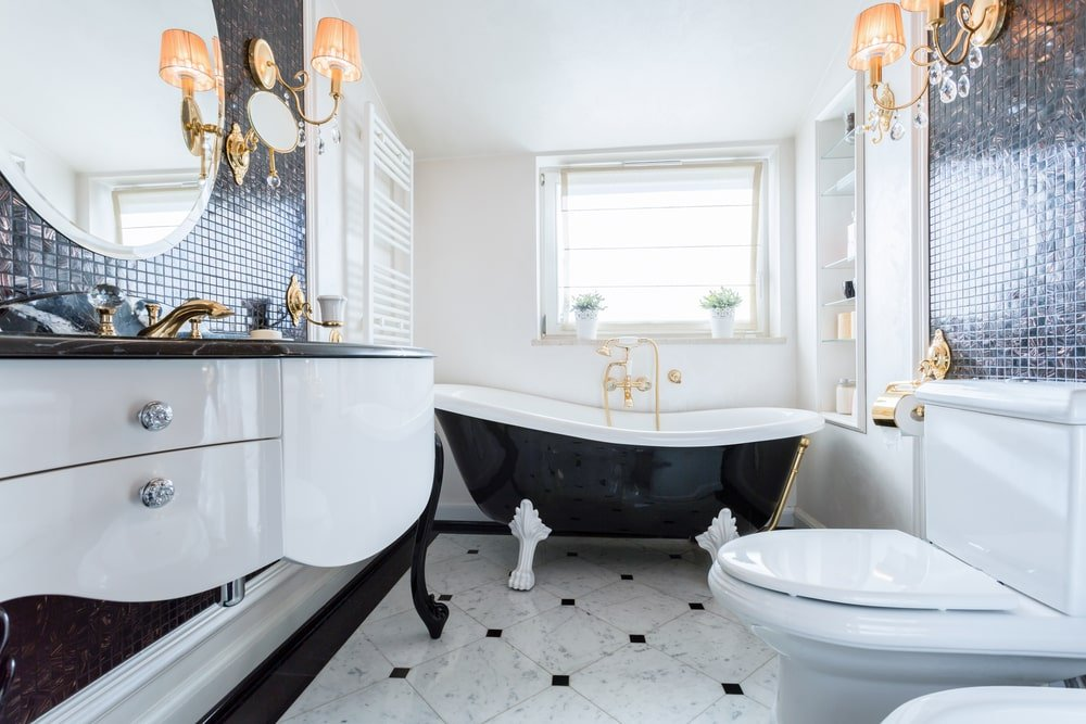 The elegant master bathroom showcases a toilet and a floating sink vanity against the black mosaic tiled wall accented with brass fixtures and sconces. There's a clawfoot tub by the picture window flanked by an inset shelf and a white towel rack.