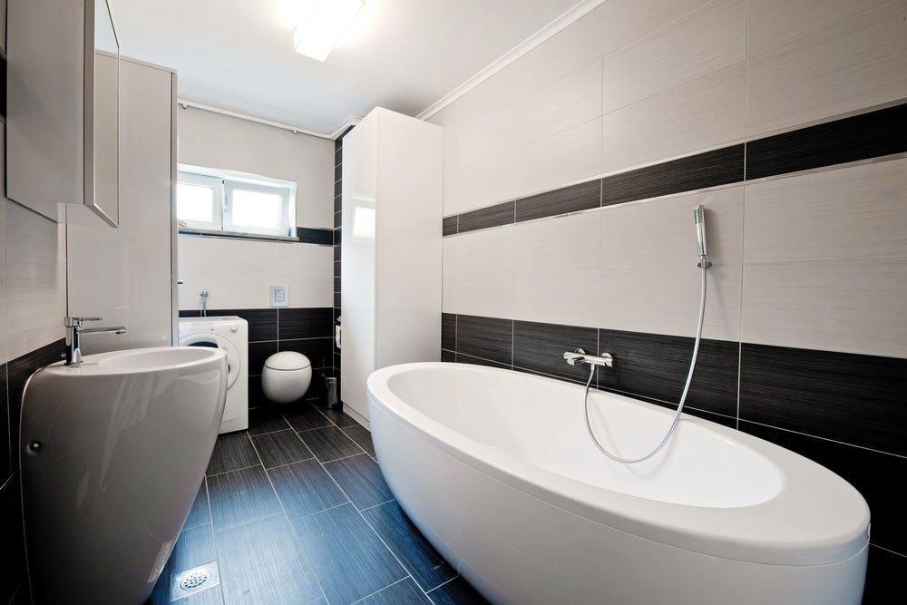 A stylish pedestal sink faces the freestanding tub against the black and white tiled walls. It is accompanied by a mirrored medicine cabinet and a front load washing machine by the glazed windows.