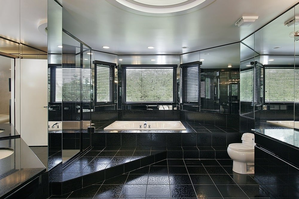The spacious master bathroom features a modern toilet and a drop-in tub blending in with the black tiled flooring. It has mirrored walls and a bay window covered with roller blinds.