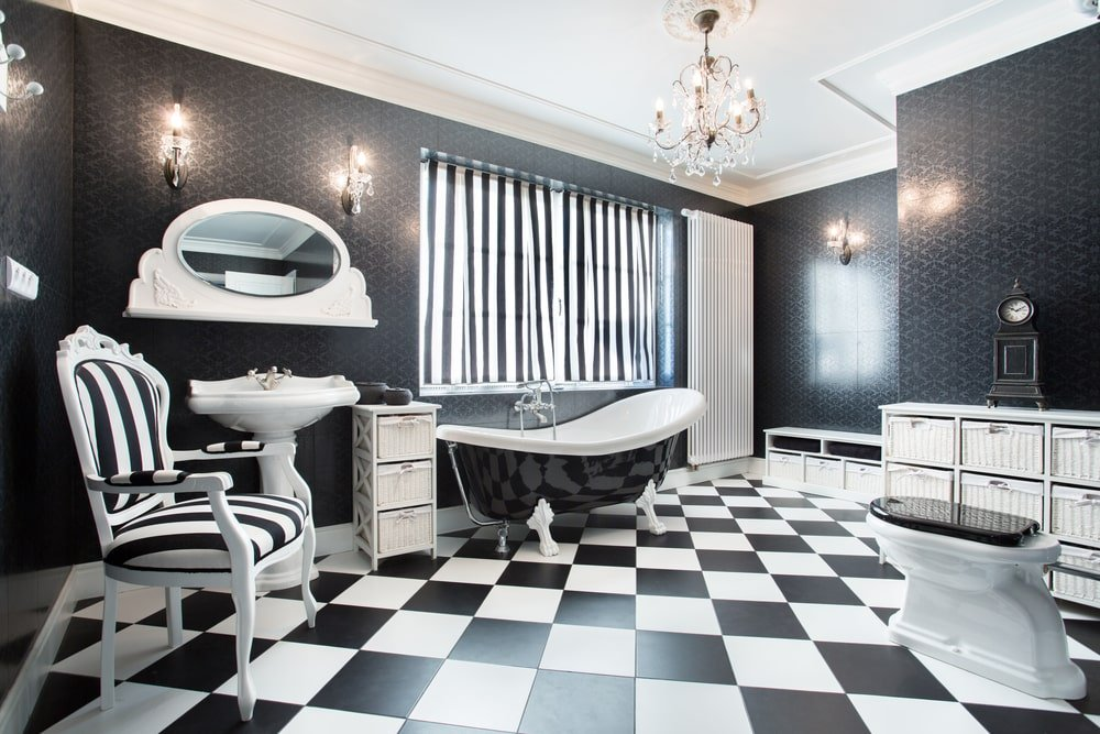 Clad in black patterned wallpaper, this master bathroom boasts a pedestal sink and a striped cushioned chair matching with the curtains above the clawfoot tub. It includes a fancy chandelier and open shelvings over checkered flooring filled with storage boxes.