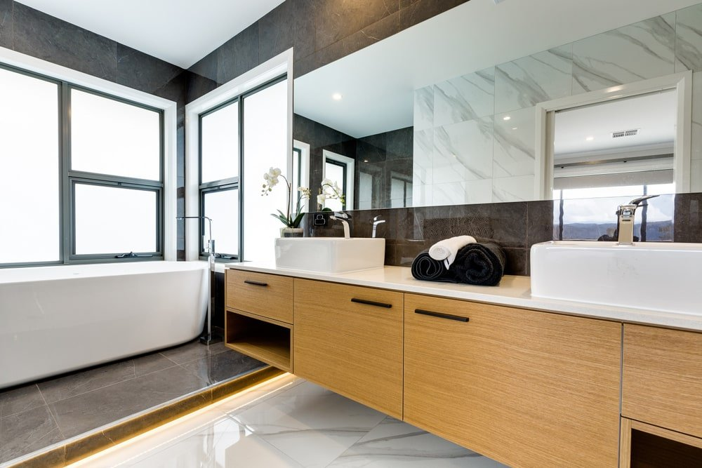 This master bathroom offers a freestanding tub and a floating vanity that's topped with dual vessel sink and a quartz countertop. It has tiled flooring and plenty of glazed windows allowing an abundance of natural light in.