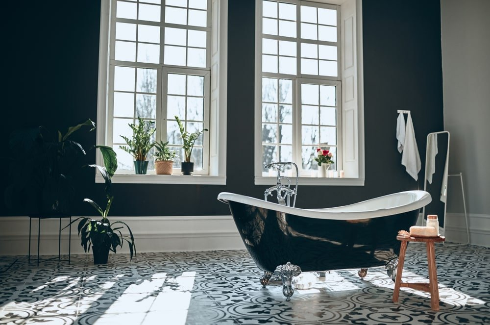 Natural light streams in through the white framed windows in this airy master bathroom with small potted plants and a black clawfoot tub with a wooden stool on the side over decorative tiled flooring.