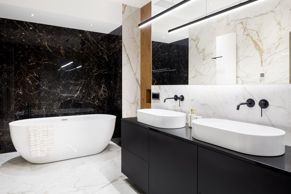 A linear pendant light illuminates the frameless mirror and dual vessel sink vanity with wrought iron fixtures. It is accompanied by a freestanding tub against the black marble wall.