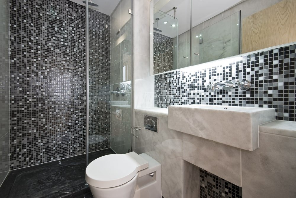 Black master bathroom with a modern toilet and a marble sink under the mirrored medicine cabinet. It includes a walk-in shower that's accented with stunning mosaic tile backsplash.