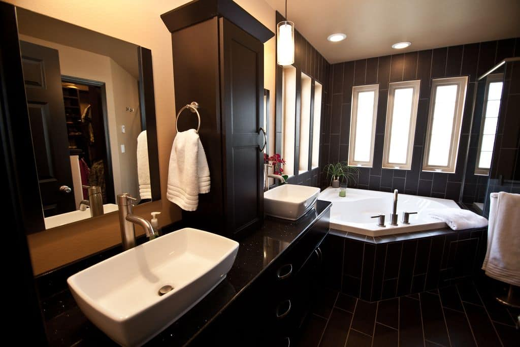 A black cabinet sits on a granite top vanity blending in with the tiled flooring and walls. There's a deep soaking tub by the glass paneled windows inviting natural light in.