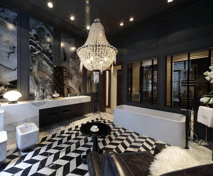 Black master bathroom designed with interesting murals and a boho chandelier that hung over the round side table. It has a drop-in tub and a marble vanity along with a leather armchair over herringbone flooring.