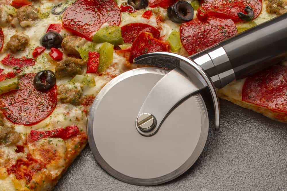 Closeup of a pizza cutter on a sliced pizza.