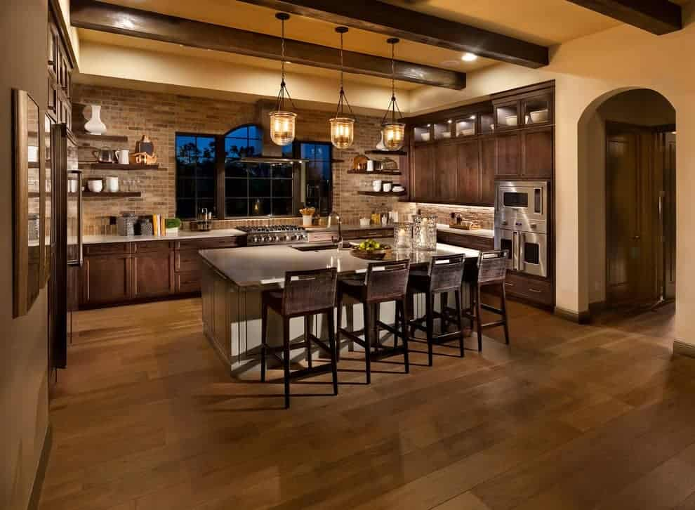 Ambient light from the glass pendant lights creates a warm and cozy feel in this kitchen with stainless steel appliances and dark wood cabinets contrasted by a white island that's lined with rustic stools.