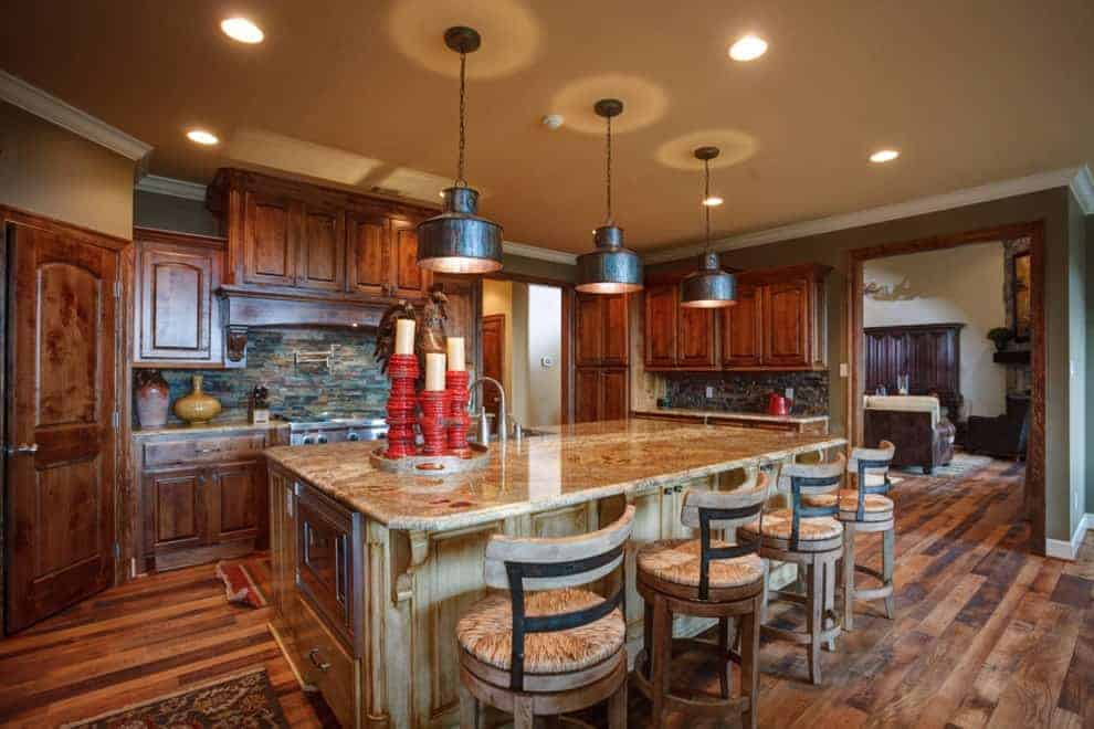 Brown kitchen offers wooden cabinetry and a distressed island paired with round counter stools. It is illuminated by bronze dome pendants and recessed ceiling lights.