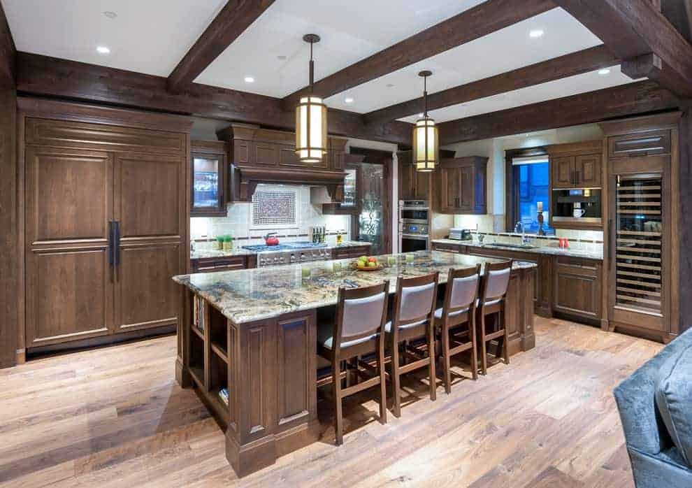 Cylindrical pendant lights illuminate the granite top island lined with cushioned counter chairs. It is accompanied by stainless steel appliances and wooden cabinetry that complements the wide plank flooring and exposed beams.