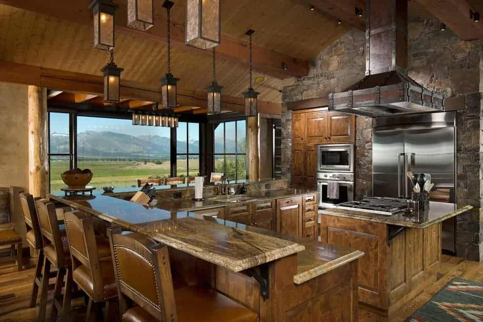 This kitchen boasts a wooden island and two-tier breakfast bar along with stainless steel appliances and plenty of pendant lights that hung from the cathedral ceiling. It has a stone accent wall and glazed windows overlooking a breathtaking mountain view.