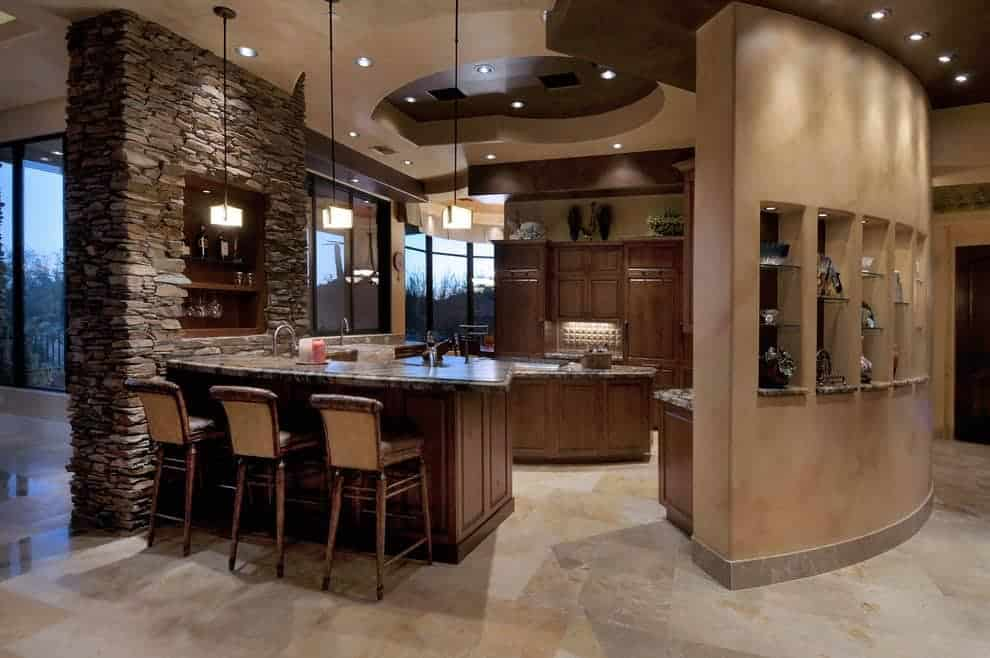 A stone brick pillar mounted with an inset shelf adds texture in this kitchen featuring granite countertops and wooden cabinetry that matches the island and peninsula. It is illuminated by cube pendants and recessed lights mounted on the tray ceiling.