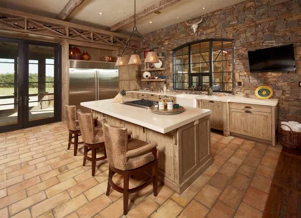 This kitchen boasts built-in wine racks arranged in a crisscross pattern along with wooden cabinets that match the breakfast island paired with wooden counter chairs. It has brick flooring and a stone accent wall mounted with a TV and an animal head decor.