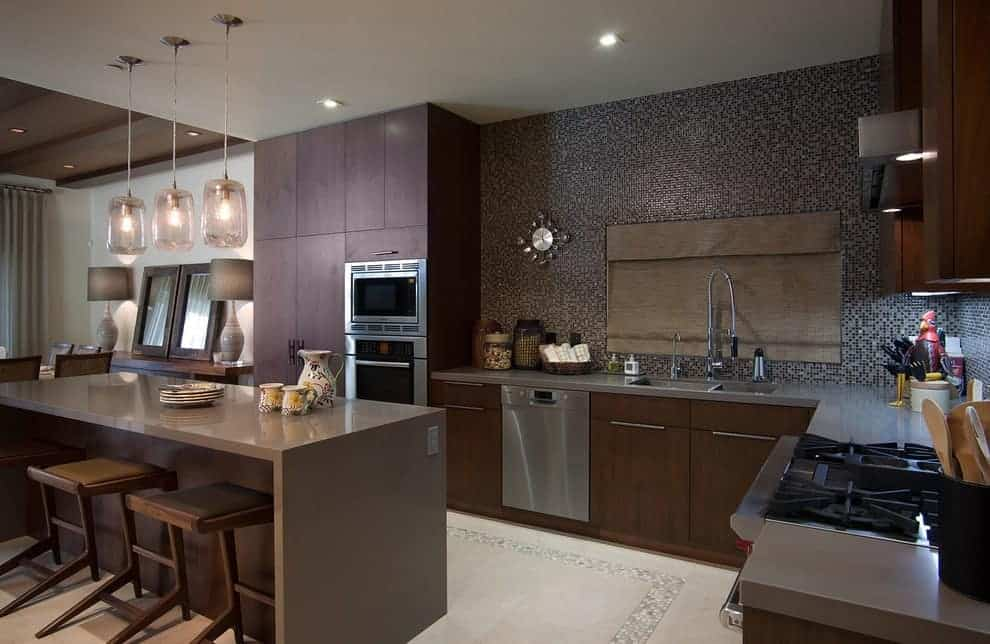 Mosaic tile backsplash mounted with a stylish clock adds a stunning accent in this contemporary kitchen with brown cabinetry and a sleek island lighted by glass pendant lights.