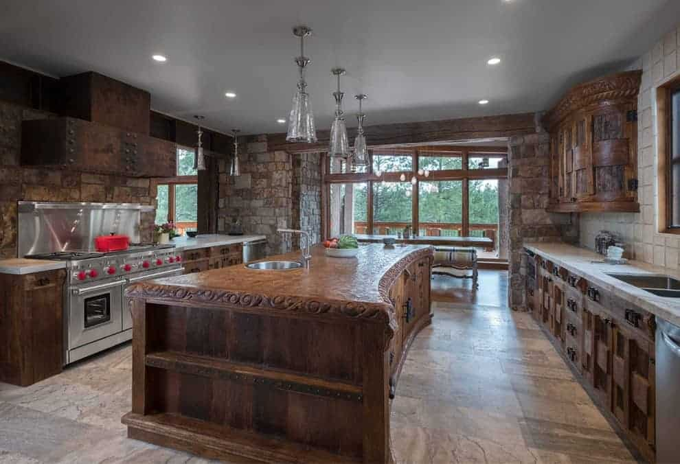 Rustic kitchen with stone brick walls and full height glazing allowing natural light in. It has stainless steel appliances and wooden cabinetry matching with the island that's illuminated by glass pendant lights.