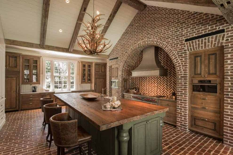 Round back counter chairs sit at a green island bar lighted by an antler chandelier that hung from the cathedral ceiling. It is accompanied by wooden cabinets and an arched cooking alcove with herringbone backsplash.