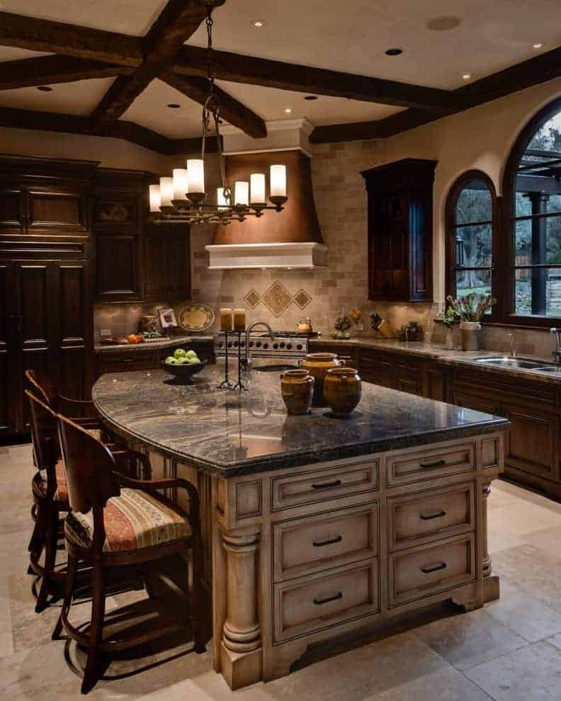 This kitchen showcases dark wood cabinets and a marble top island lighted by a wrought iron chandelier that hung from the wood beam ceiling. It includes cushioned counter chairs and a brown range hood fixed against the brick backsplash.
