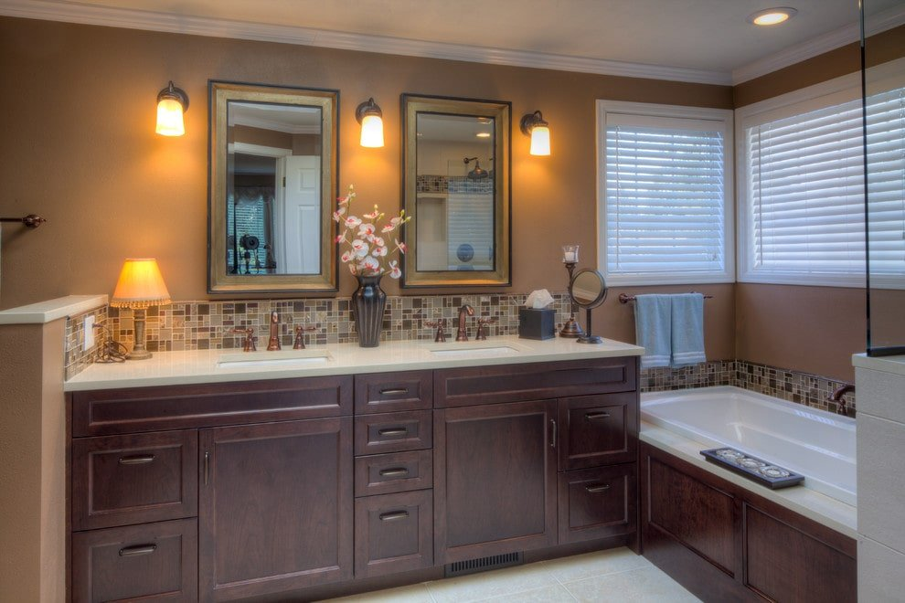 Warm sconces flank the rectangular mirrors hanging above a dark wood vanity with dual sink and copper fixtures. There's a deep soaking tub on the side accented with mosaic tile backsplash.