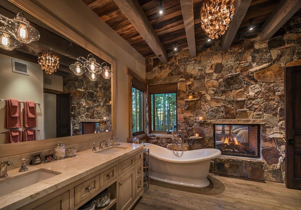 The rustic primary bathroom features a freestanding tub and a dual-sided fireplace fixed on the stone accent wall. It includes a dual sink vanity and a shell chandelier that hung from the wood beam ceiling.