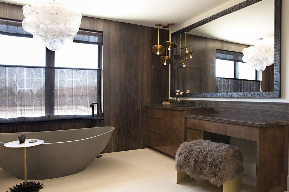 A faux fur stool sits at a dark wood vanity lighted by brass pendant lights. It is accompanied by a bubble chandelier and a freestanding tub complemented by a round side table.