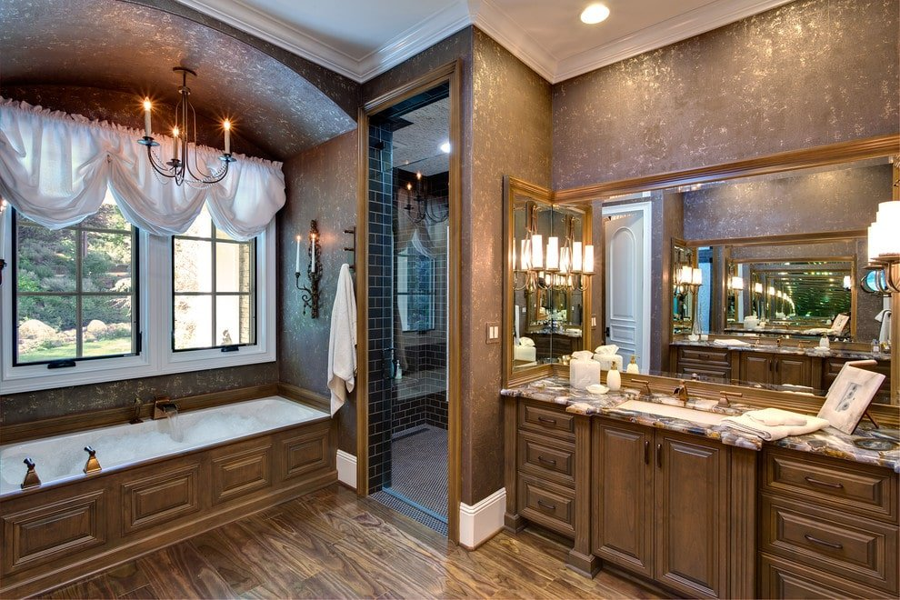 A wooden sink vanity and an alcove tub flanked the walk-in shower that's clad in black subway tiles. This room has hardwood flooring and white framed windows dressed in white roman shades.