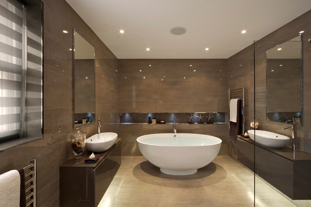 Brown master bathroom boasts a freestanding tub by the inset shelf illuminated by recessed lights. It includes facing vanities with vessel sinks and rectangular mirrors mounted on the tiled walls.
