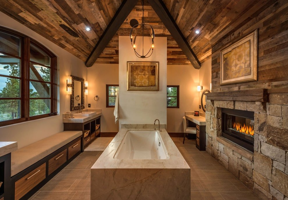 Cozy primary bathroom with a window seat nook and a drop-in tub lighted by a wrought iron chandelier that hung from the wood beam ceiling. It is completed with marble top vanities and a stone brick fireplace with a framed artwork on top.