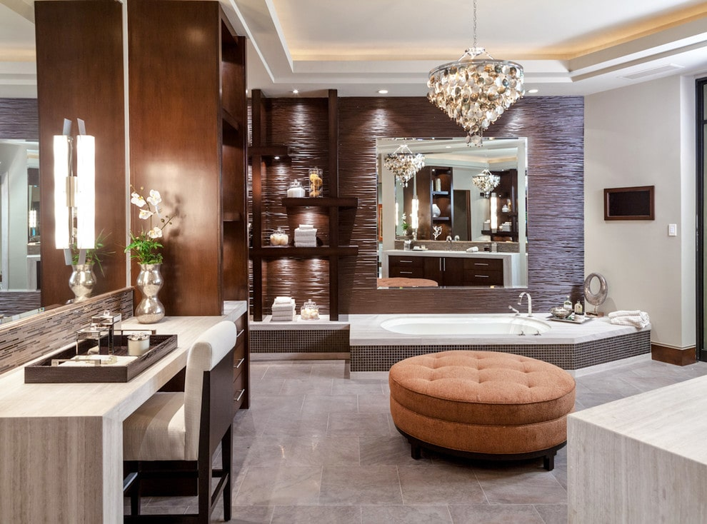 Deluxe master bathroom offers a drop-in tub and light wood vanity paired with a cushioned chair. There's a round tufted ottoman in the middle lighted by a gorgeous chandelier that hung from the tray ceiling.