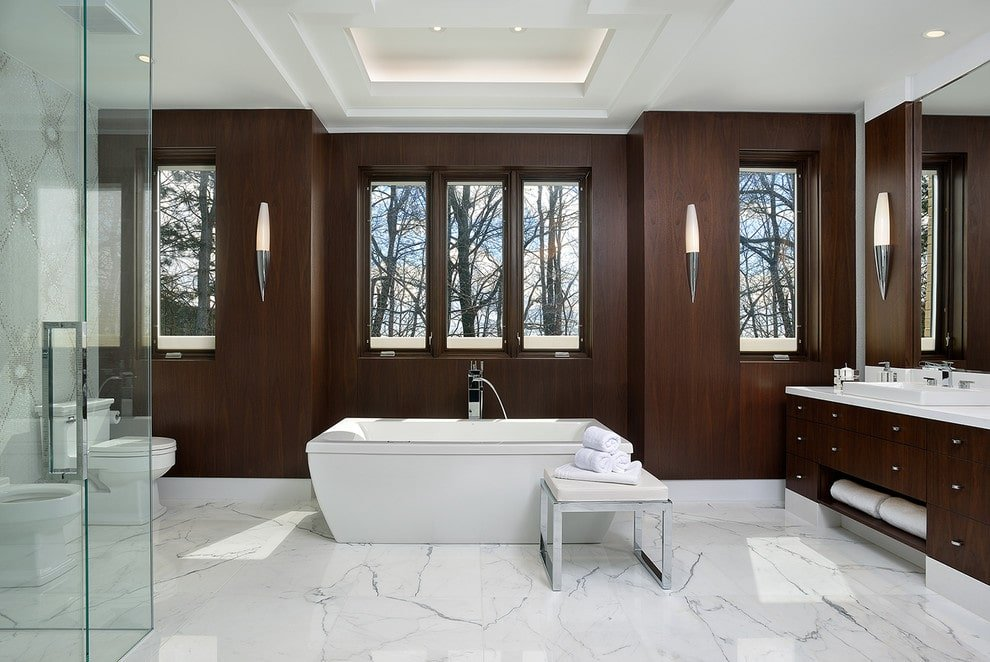 The brown master bathroom features a walk-in shower and a freestanding tub paired with a chrome cushioned stool over marble tiled flooring. It includes a traditional toilet and a dark wood vanity lighted by sleek sconces.