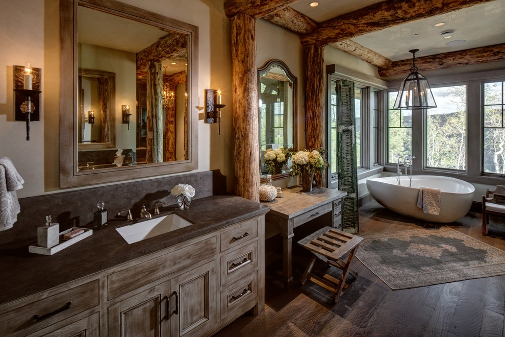 Rustic primary bathroom with exposed wood beams and wide plank flooring topped by a vintage rug. It includes wooden vanities and a freestanding tub by the glazed windows lighted by a glass pendant.