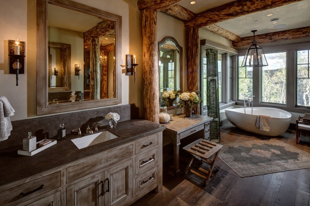Rustic master bathroom with exposed wood beams and wide plank flooring topped by a vintage rug. It includes wooden vanities and a freestanding tub by the glazed windows lighted by a glass pendant.