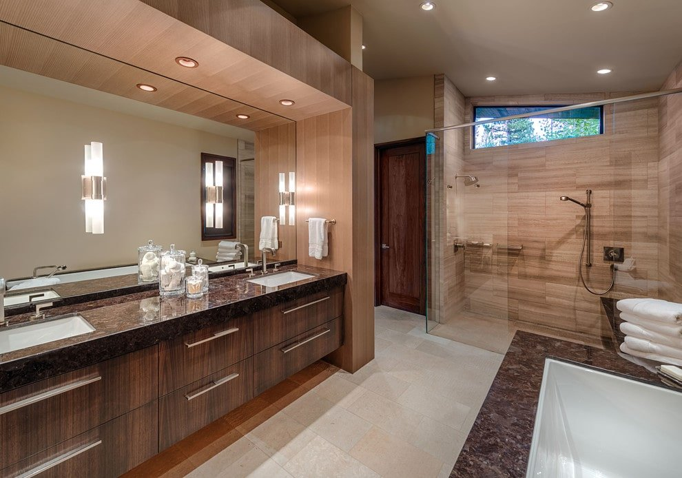 Sleek master bathroom boasts a walk-in shower enclosed in frameless glass panels. It includes a drop-in tub and a dark wood vanity topped with dual sink and granite countertop.