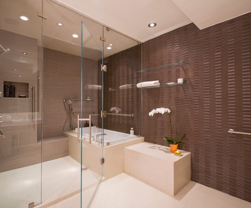 This primary bathroom showcases a tiled bench under floating glass shelves along with a deep soaking tub that's integrated with a shower. It is illuminated by recessed lights mounted on the regular beige ceiling.