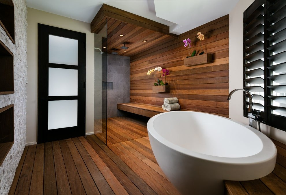 A black glazed door opens to this primary bathroom with wide plank flooring and inset shelves fitted on the white brick wall. It includes a walk-in shower and a freestanding tub by the louvered window.