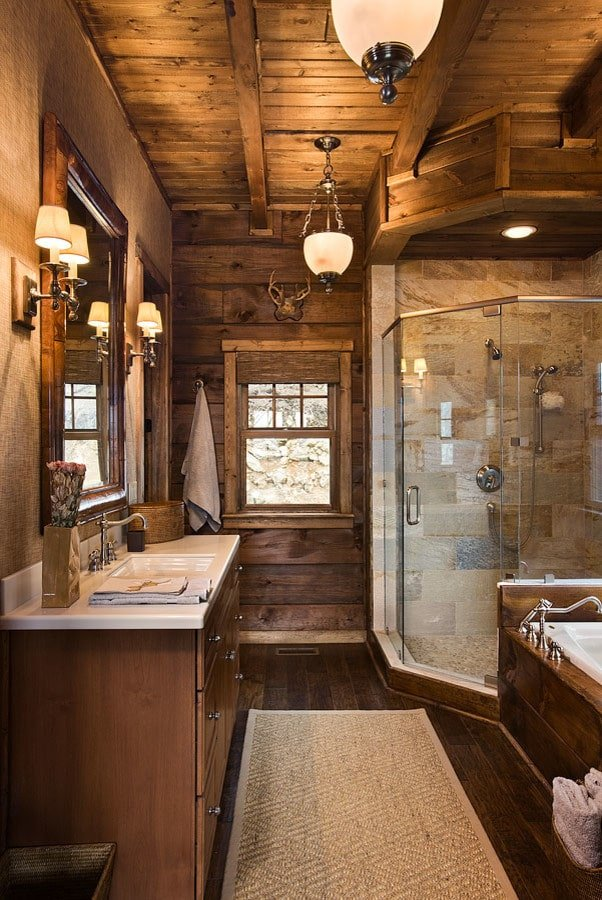 Warm sconces flank a wooden framed mirror hanging above the sink vanity with quartz countertop. It faces the patterned rug and a deep soaking tub next to the walk-in shower.