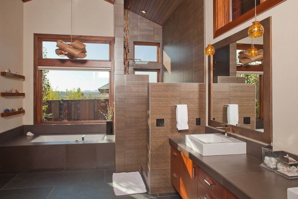 Contemporary master bathroom illuminated by amber pendant lights and a stylish chandelier that hung over the drop-in tub by the glazed window. It has a walk-in shower and a vessel sink vanity paired with a wooden framed mirror.