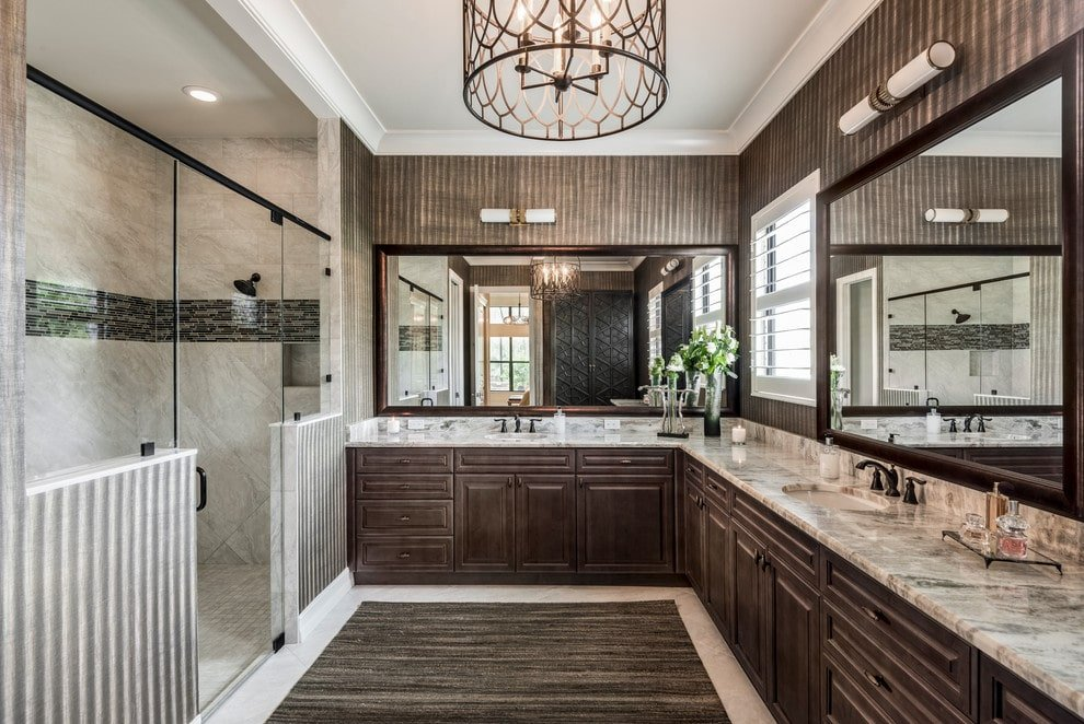 A walk-in shower and granite top vanities surround a brown area rug that lays on the white tiled flooring. It is illuminated by a drum chandelier and linear sconces mounted on the striped walls.