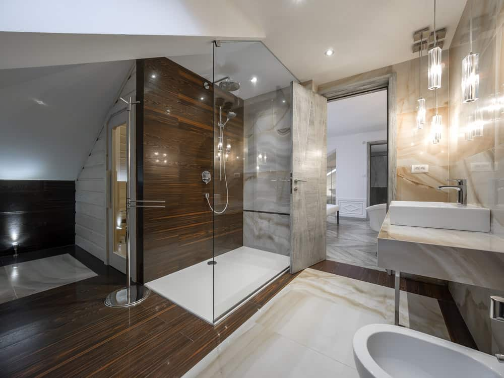 A gray door opens to this primary bathroom with a toilet and vessel sink lighted by glass pendant lights. It includes a walk-in shower situated next to the sauna room.