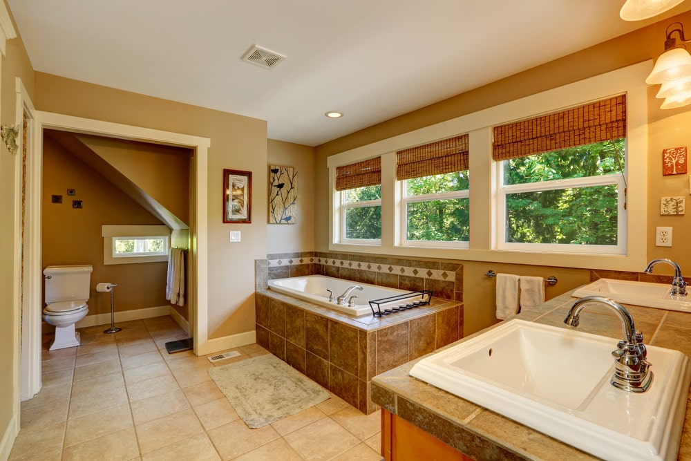 The warm primary bathroom showcases a toilet area and a dual sink vanity facing the deep soaking tub highlighted by lovely artworks. It has beige tiled flooring and glazed windows covered in wicker roman shades.