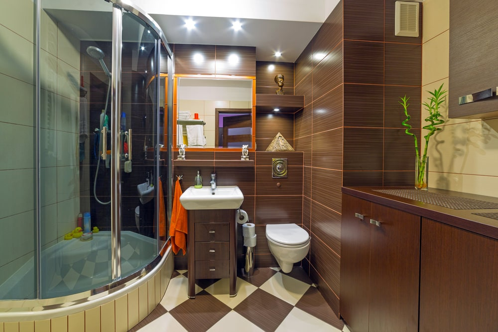 A walk-in shower and wall hung toilet flank a three-drawer pedestal sink over checkered flooring. It is fixed under a floating shelf and orange framed mirror that's mounted on the brown tiled wall.