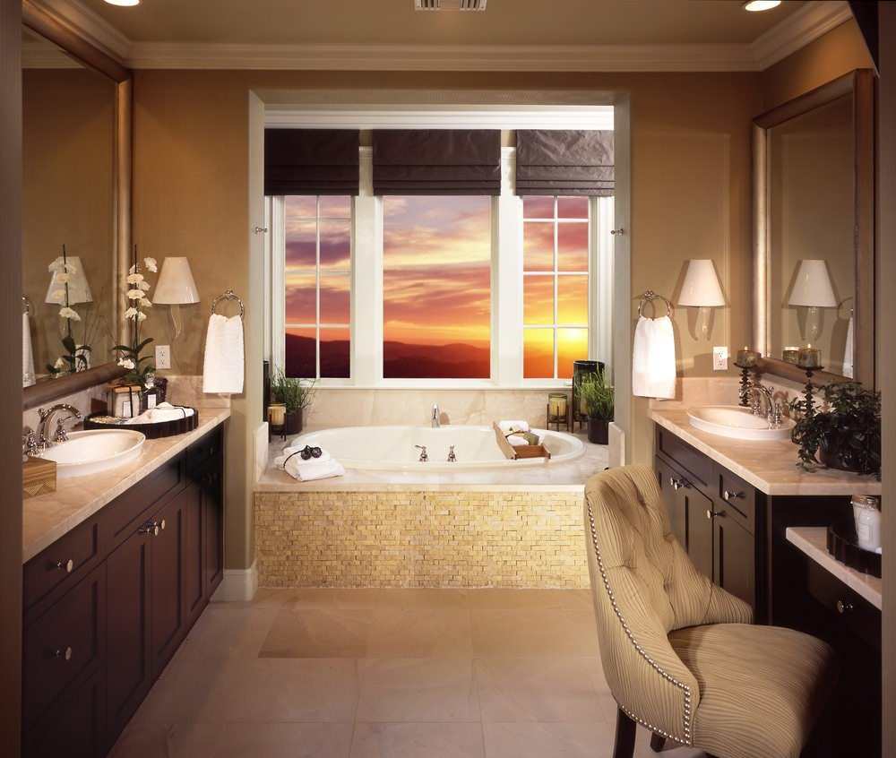This primary bathroom features a comfy tufted chair and dark wood vanities facing each other. It includes a deep soaking tub by the white framed windows covered in brown roman shades.