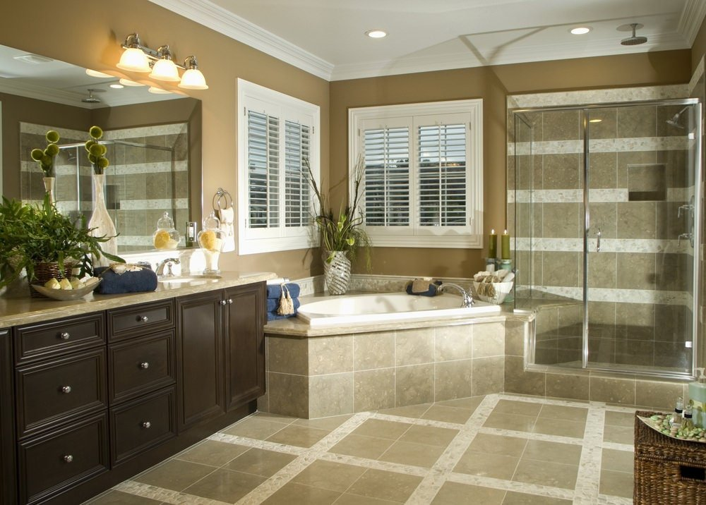 Brown primary bathroom with a corner tub by the white framed windows flanked by a walk-in shower and granite top vanity. It is illuminated by chrome sconces and recessed ceiling lights.