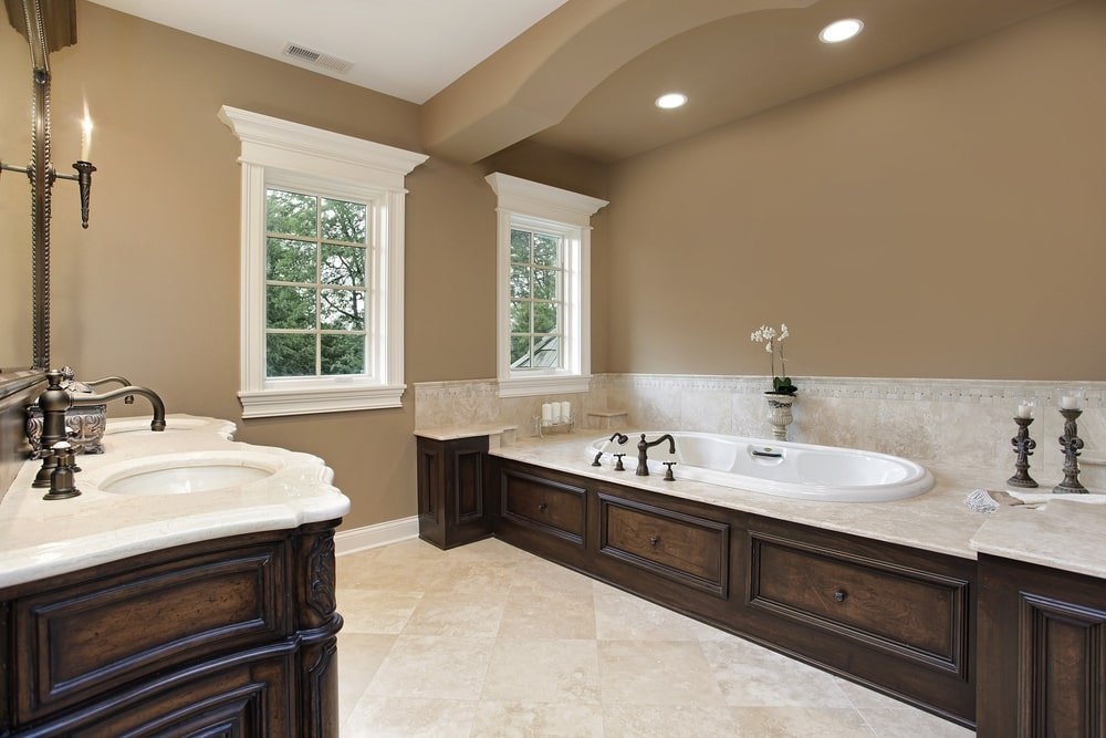 A dual sink vanity faces the deep soaking tub fitted with bronze fixtures. It is illuminated by recessed ceiling lights along with natural light from the white framed windows.