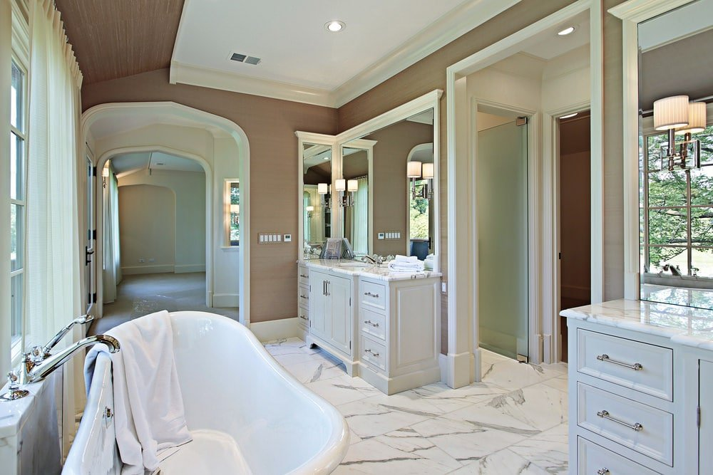 Airy master bathroom offers his and her sink vanity along with a freestanding tub over white marble tiled flooring. It has brown walls and glazed windows allowing natural light in.