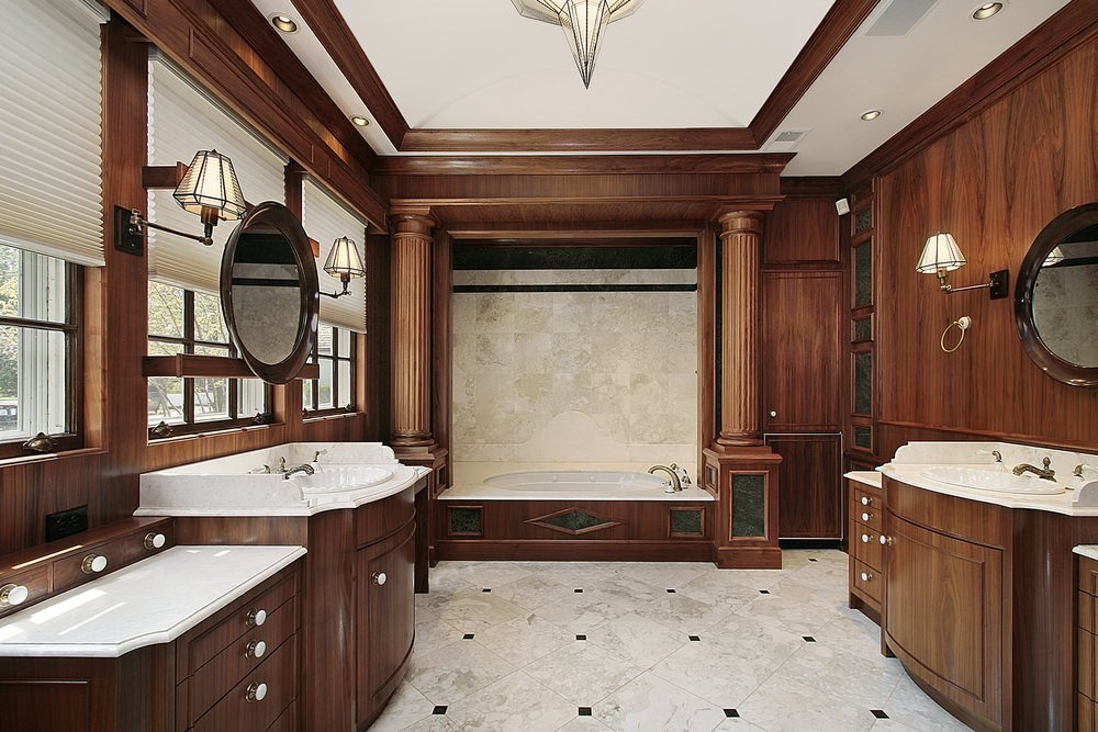 Round mirrors flanked by wall sconces hang above the sink vanities that blend in with the wood paneled walls. This primary bathroom features an alcove tub against the marble tiled wall lined with brown columns.