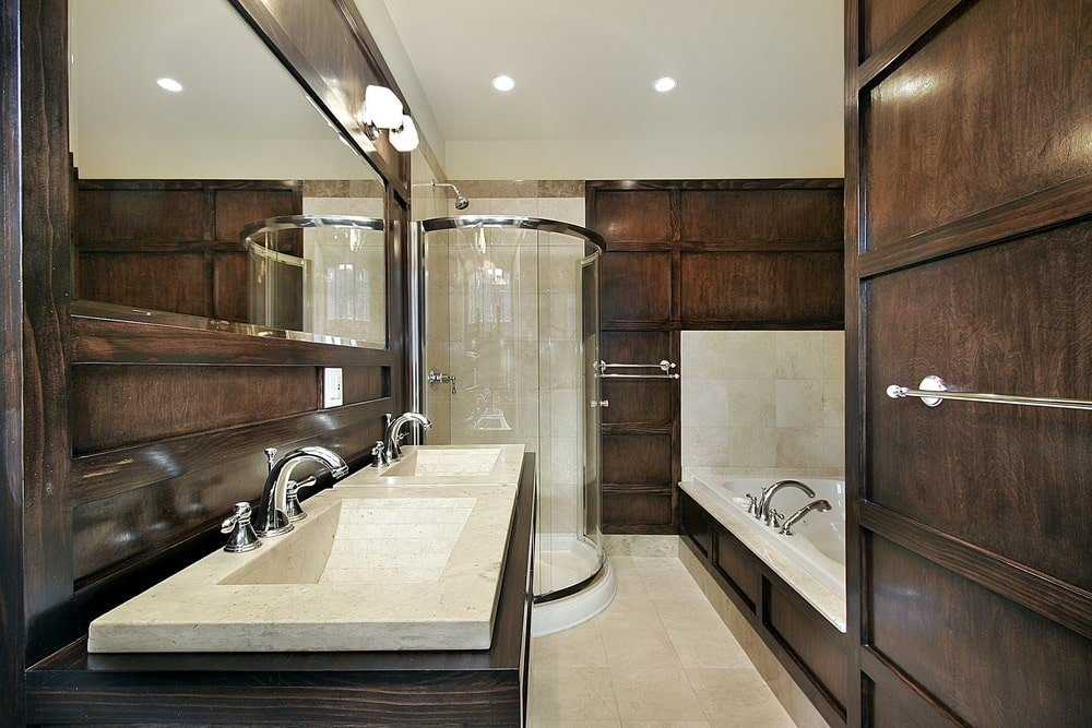 A chrome framed mirror hangs above the dark wood vanity that's topped with dual sink. It is accompanied by a deep soaking tub and a walk-in shower enclosed in a curved glass panel.