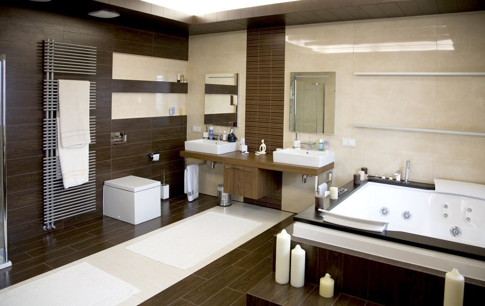 Brown master bathroom with a whirlpool tub and a modern toilet that sits next to the stainless steel towel rack. It includes a dual vessel sink vanity paired with frameless mirrors.