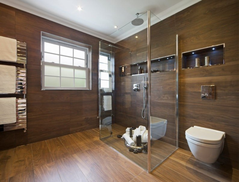 This primary bathroom offers a walk-in shower and a wall hung toilet fixed under the inset shelf. It has hardwood flooring and wood paneled walls fitted with a white framed window.
